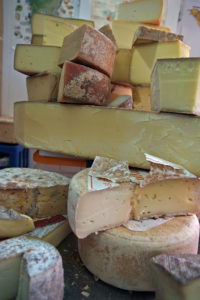 Shop display of various hard cheeses.